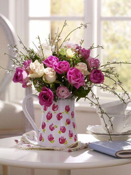 Троянди в керамічному глечику в інтер'єрі кухні