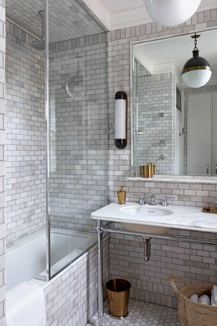 Освітлення у маленькій ванній з оздобленими цеглою стінами