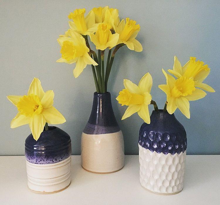 Жовті нарциси у декількох вазочках