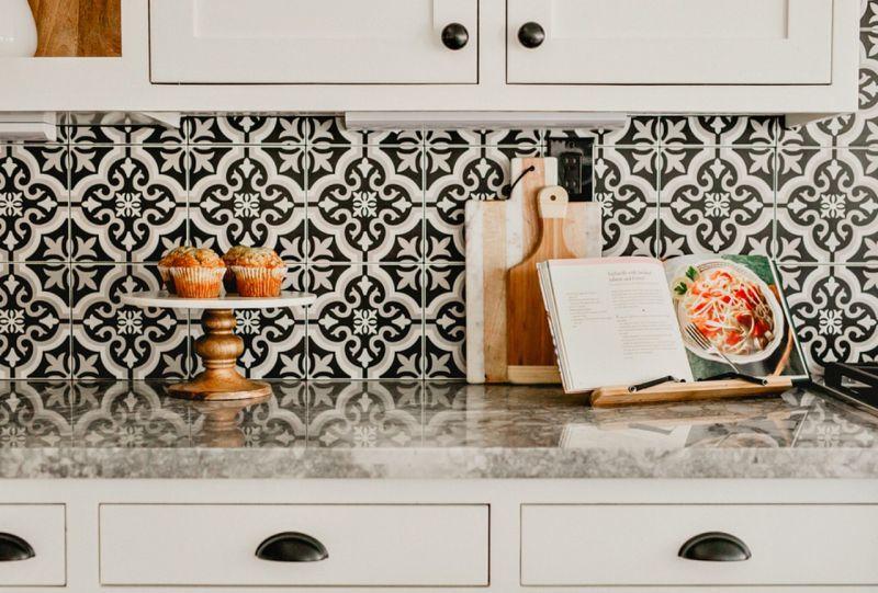 Чорно-біла цементна плитка створює стильний кухонний фартух над робочою поверхнею
