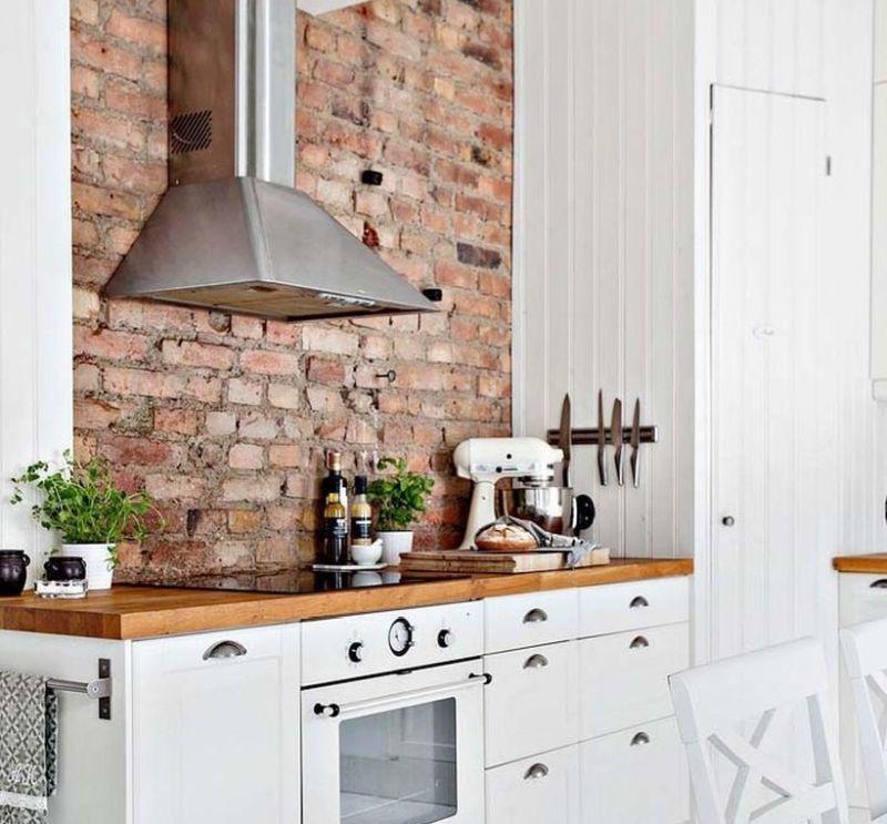Груба фактурна цегла над робочою поверхнею у сучасній кухні