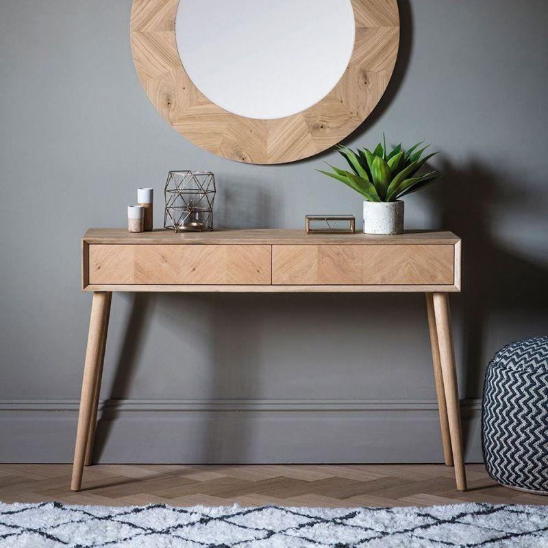 Кругле дзеркало у фактурні дерев'яній рамі над консольним столиком