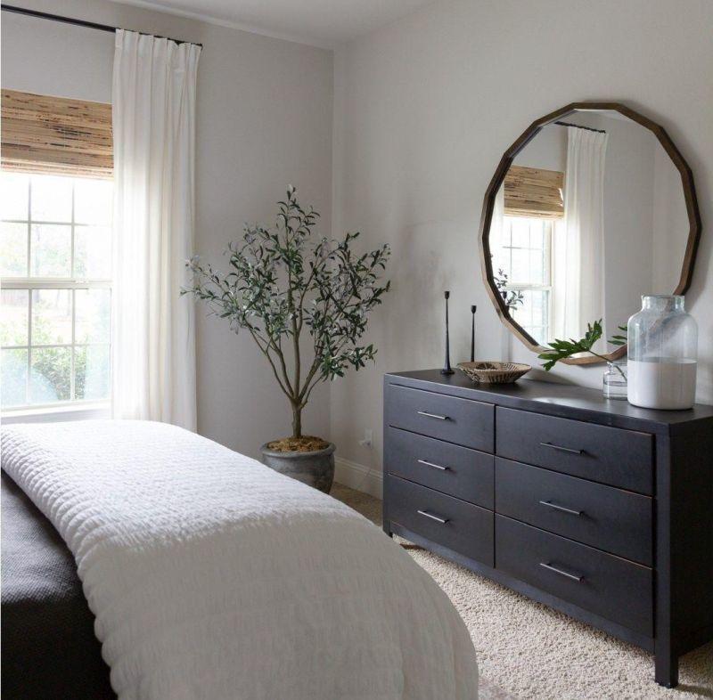 Дзеркало круглої форми над комодом у спальні