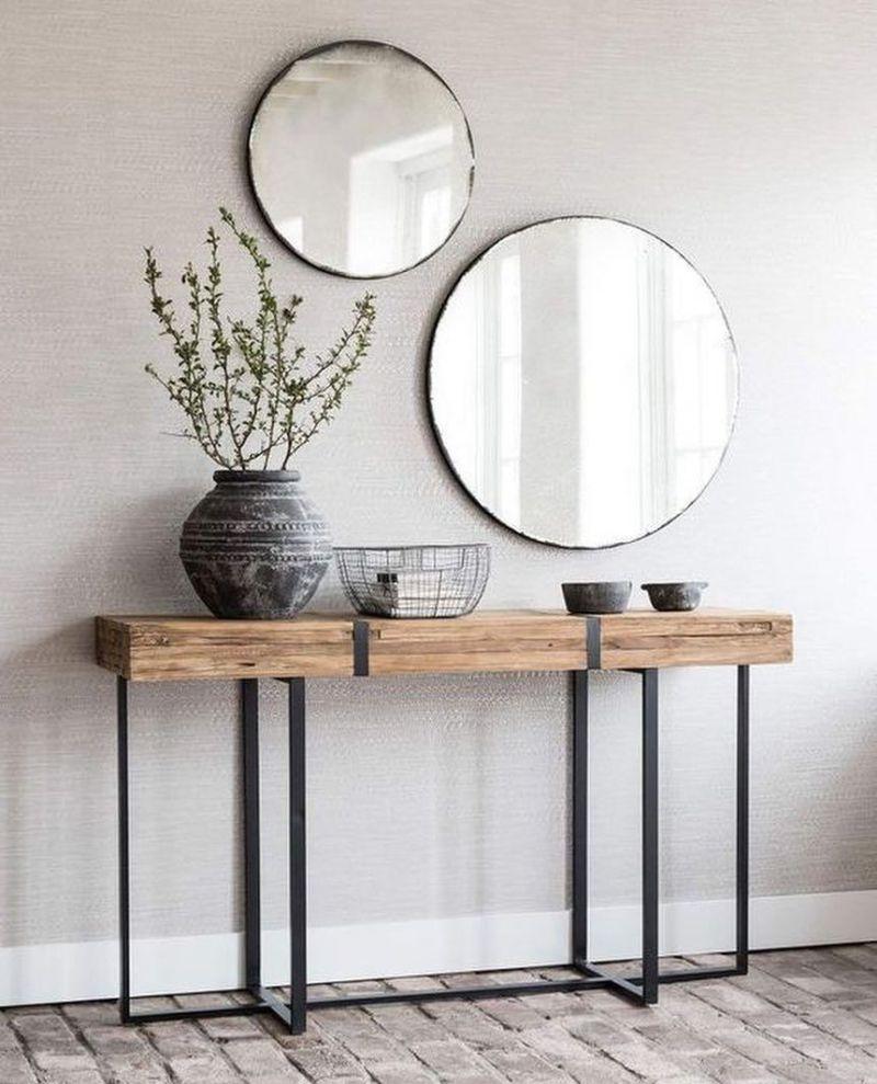 Пара круглих дзеркал різного розміру над консоллю з грубої деревини. Примітивна кераміка та дротяний кошик завершують декоративну композицію.