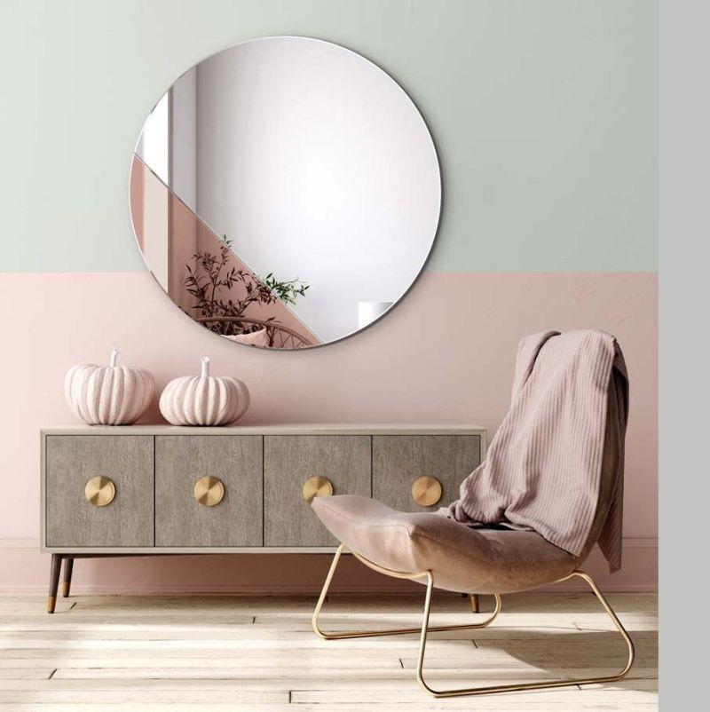 Велике дзеркало круглої форми, розташоване напроти вікна у вітальні, візуально розширює кімнату й додає світла.