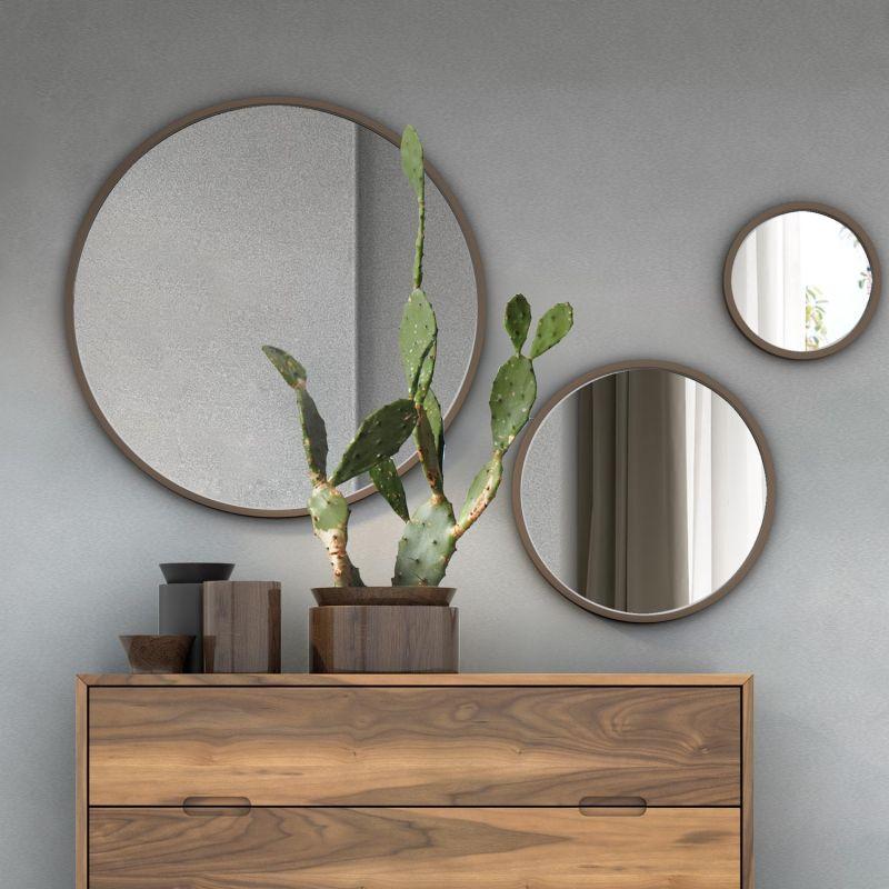 Три різновеликі круглі дзеркала в мінімалістському інтер'єрі