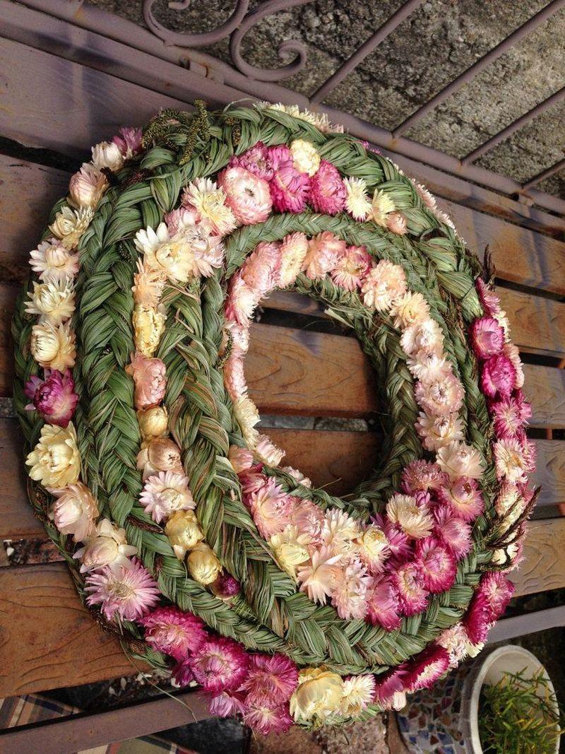 М'які відтінки сухих квітів оригінально поєднуються з фактурністю сплетених з трави кіс.