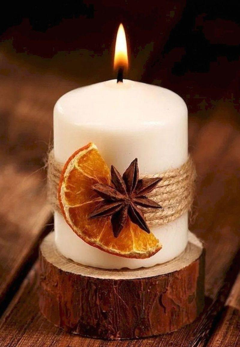 Свічка білого кольору, декорована сухим шматочком апельсина, бадьяном і мотузкою.