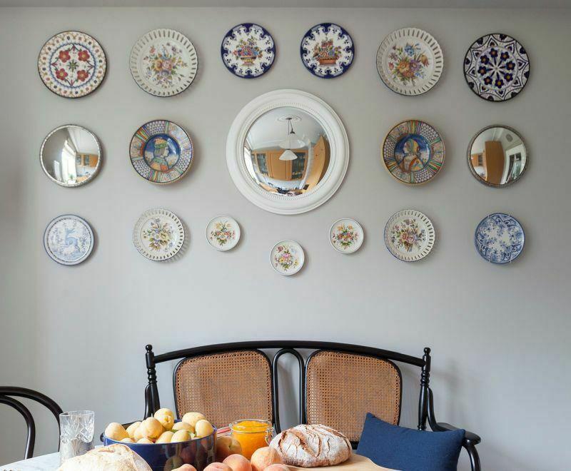 Стіна, декорована композицією з тарілок і дзеркал