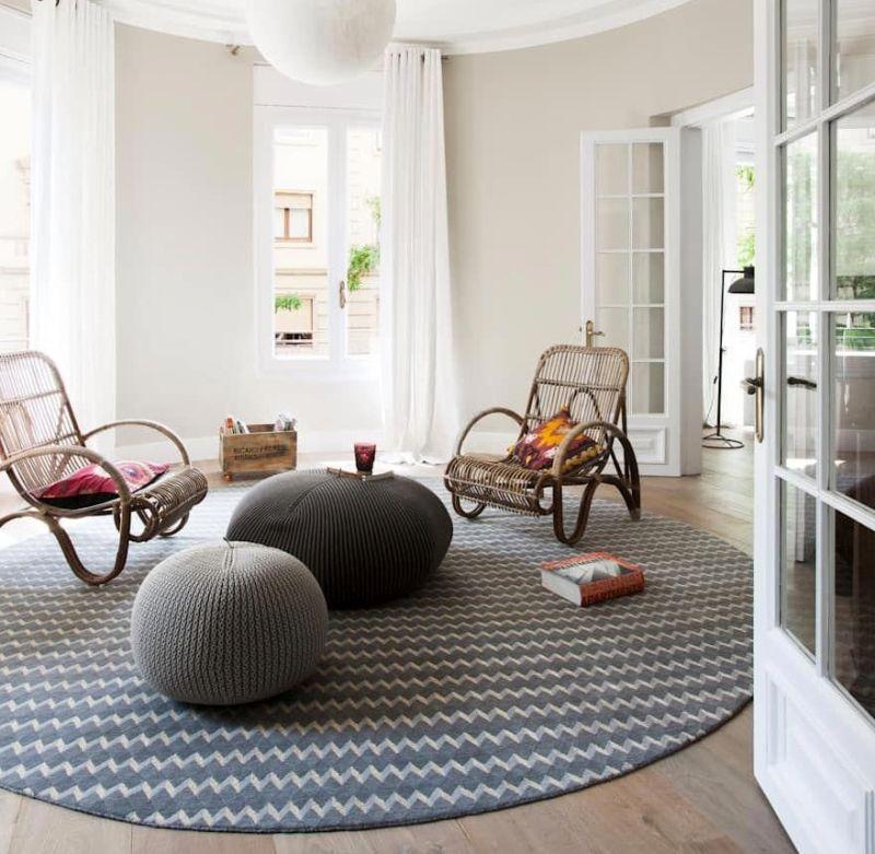 Крісла та пуфи у поєднанні з круглим килимом у вітальні