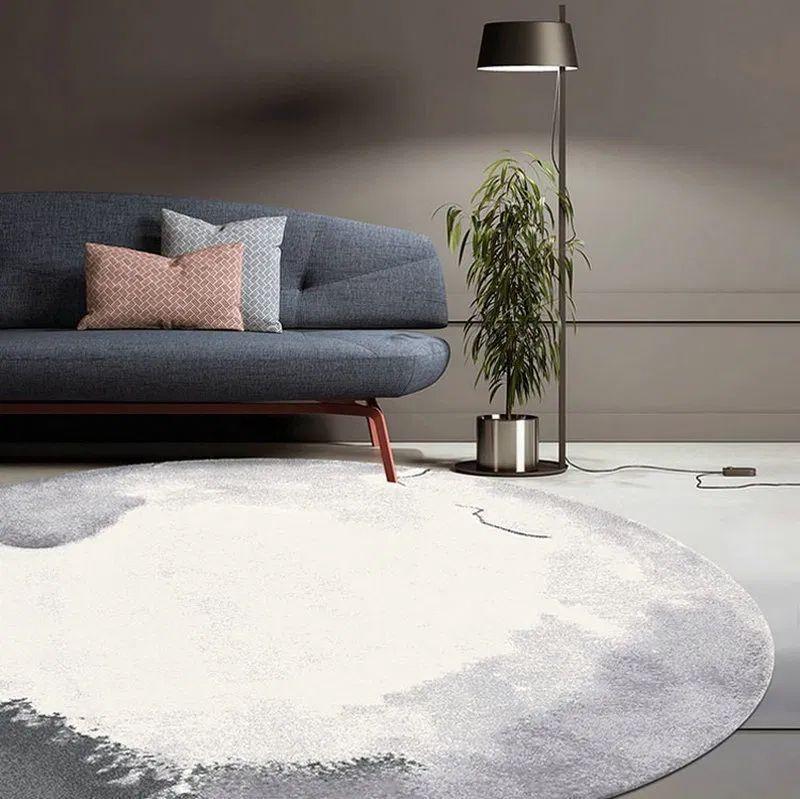 Круглий килим з абстрактним дизайном у вітальні біля дивану