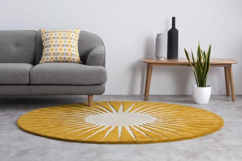 Яскравий жовтий килим круглої форми у вітальні