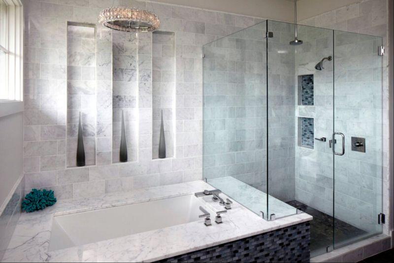 Скляна перегородка відокремлює душ від ванни у маленькій кімнаті